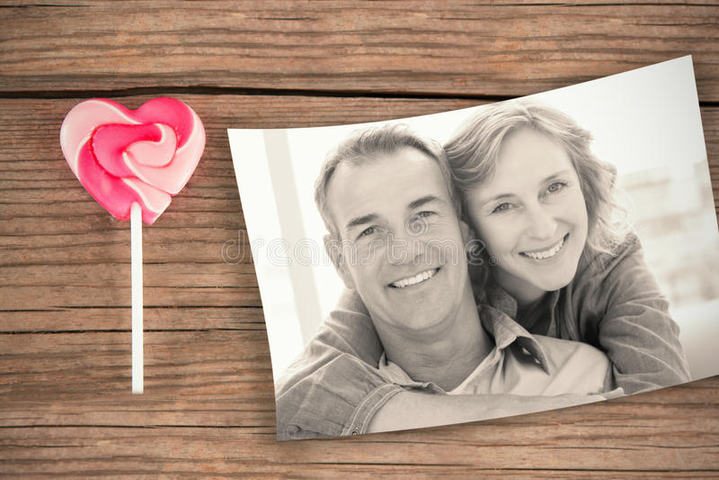 Samengesteld beeld van glimlachende vrouw die haar echtgenoot op de laag erachter koesteren van stock fotografie