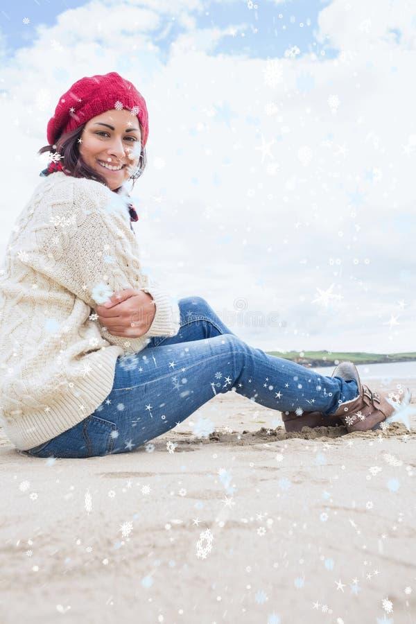Samengesteld beeld van glimlachende vrouw in modieuze warme kledingszitting op strand stock afbeeldingen