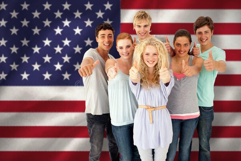 Samengesteld beeld van groep tieners die zich voor de camera met omhoog duimen bevinden stock fotografie