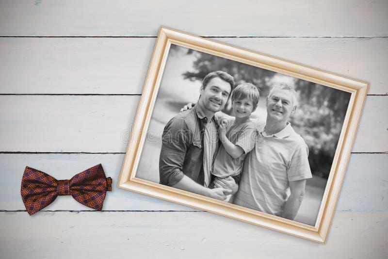 Samengesteld beeld van grootvadervader en zoon met familie op achtergrond bij park stock fotografie