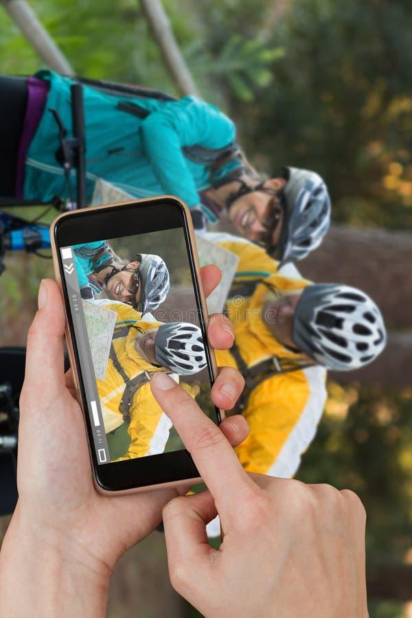 Samengesteld beeld van handen wat betreft slimme telefoon stock foto's