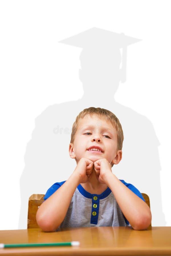 Samengesteld beeld van het glimlachen leerlingszitting bij zijn bureau stock fotografie