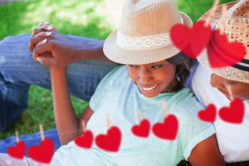 Samengesteld beeld van het glimlachen paar het ontspannen in hun tuin stock illustratie