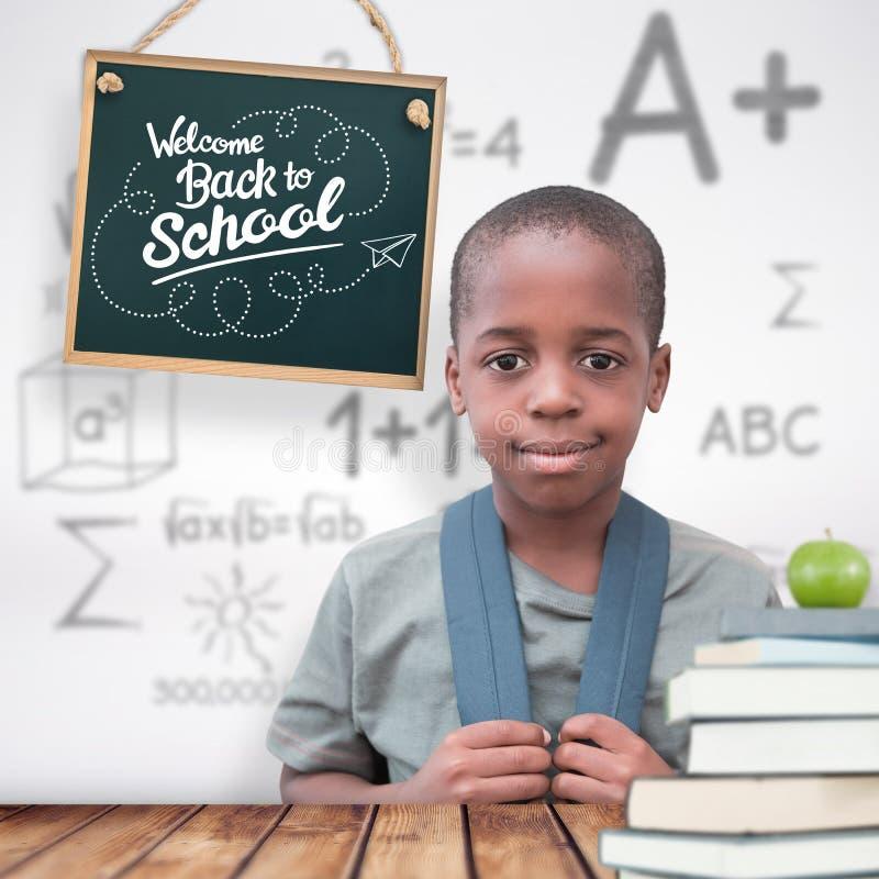 Samengesteld beeld van het leuke leerling glimlachen bij camera stock foto's