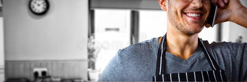 Samengesteld beeld van het mannelijke kelner spreken op mobiele telefoon stock afbeeldingen