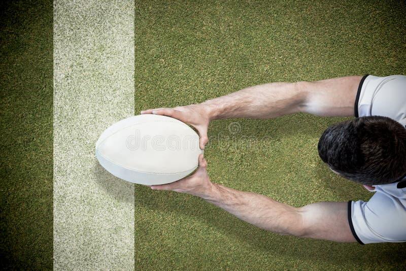 Samengesteld beeld van hoge hoekmening van het rugbybal van de mensenholding met beide handen stock afbeelding