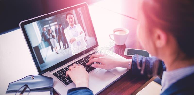 Samengesteld beeld van hoge hoekmening van vrouwelijke student die laptop op bureau met behulp van stock afbeeldingen