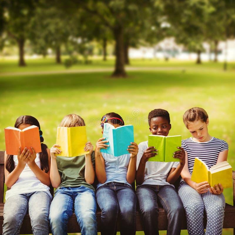 Samengesteld beeld van kinderen die boeken lezen bij park stock fotografie