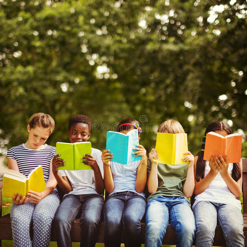 Samengesteld beeld van kinderen die boeken lezen bij park stock afbeeldingen