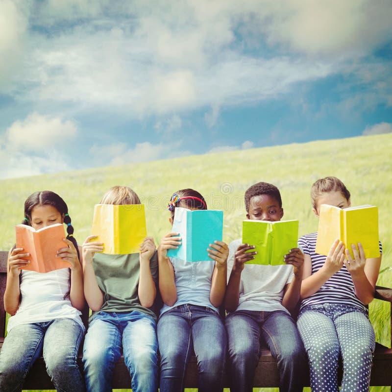 Samengesteld beeld van kinderen die boeken lezen bij park royalty-vrije stock afbeeldingen