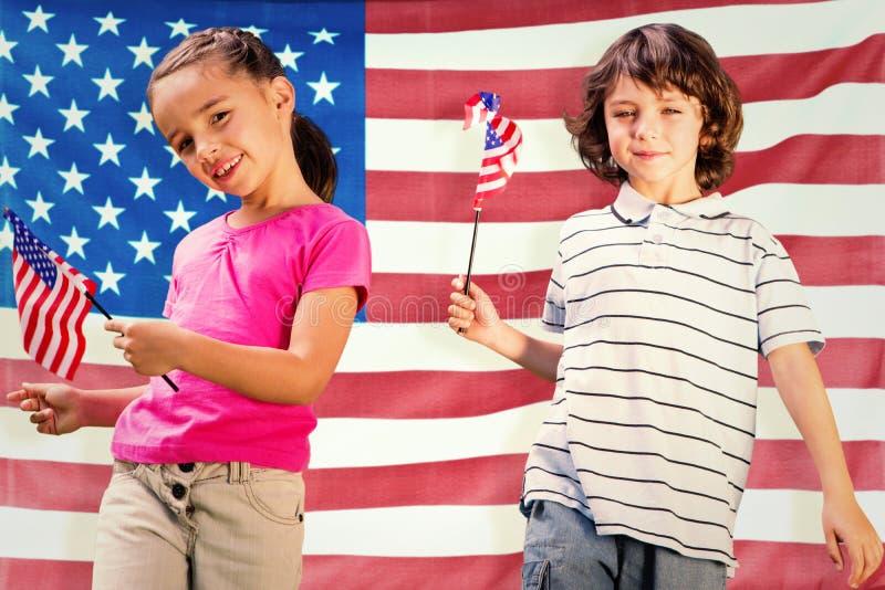 Samengesteld beeld van kinderen met Amerikaanse vlaggen stock foto's