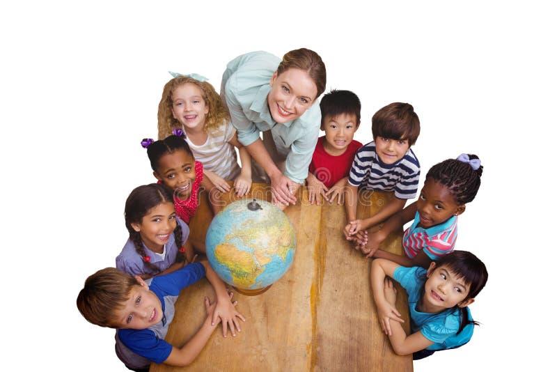 Samengesteld beeld van leuke leerlingen die rond een bol in klaslokaal met leraar glimlachen royalty-vrije stock afbeeldingen