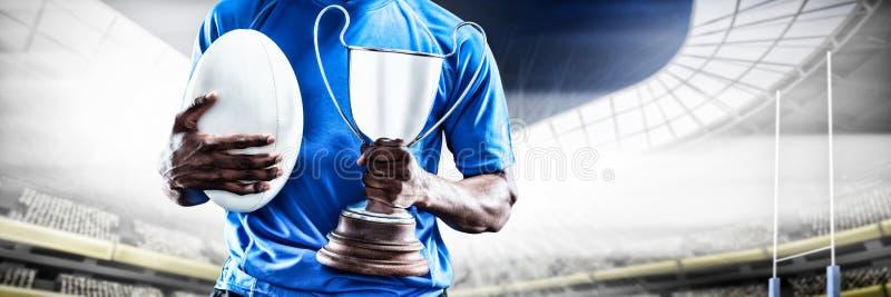 Samengesteld beeld van medio sectie van de trofee van de sportmanholding en rugbybal stock afbeeldingen