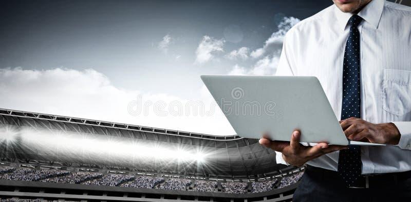 Samengesteld beeld van mid-section van de bedrijfsmens die laptop met behulp van stock foto's