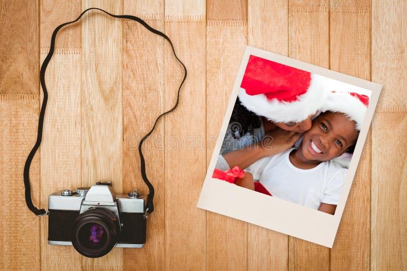 Samengesteld beeld van moeder die haar dochter kussen bij Kerstmis royalty-vrije stock afbeelding