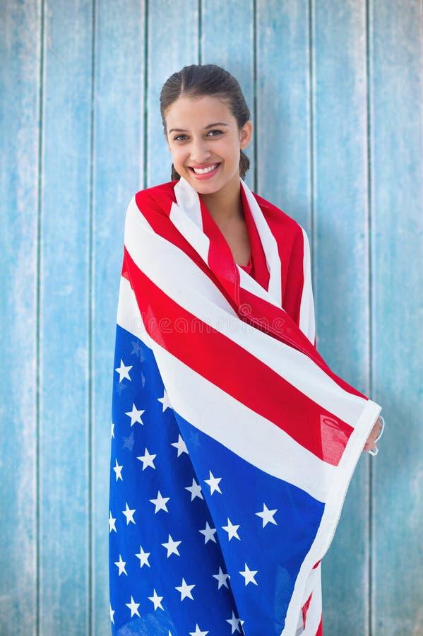 Samengesteld beeld van mooi brunette die de Amerikaanse vlag dragen royalty-vrije stock foto