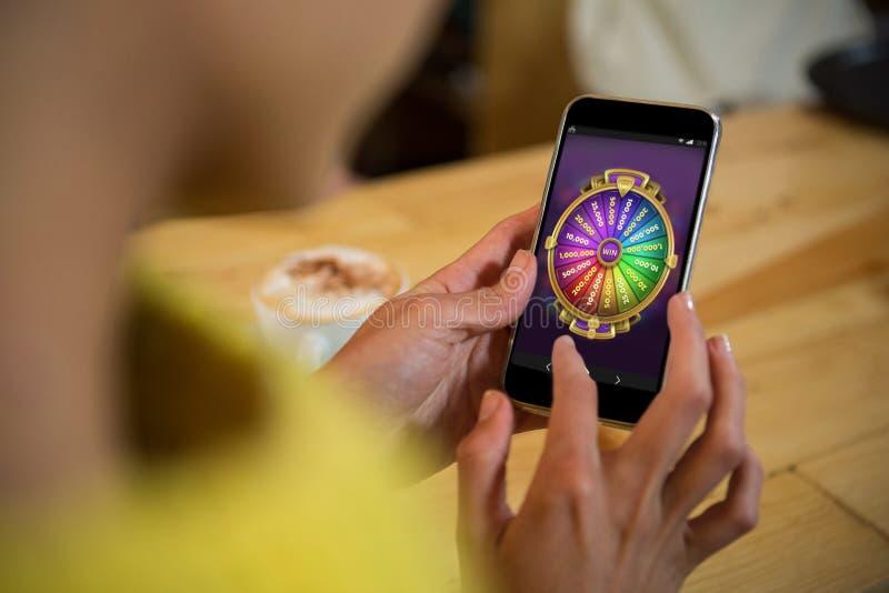 Samengesteld beeld van multi gekleurd fortuin van wiel op mobiele vertoning stock foto