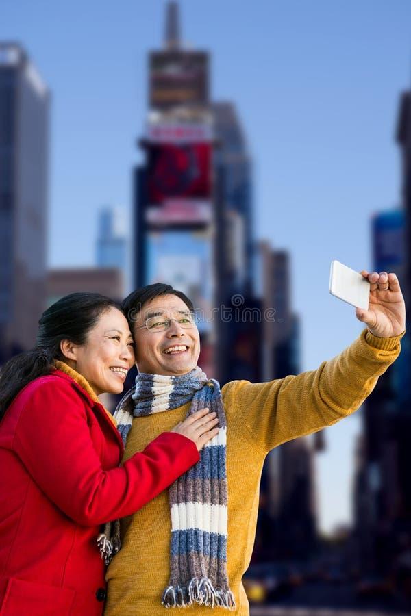 Samengesteld beeld van ouder Aziatisch paar op balkon die selfie nemen royalty-vrije stock afbeeldingen