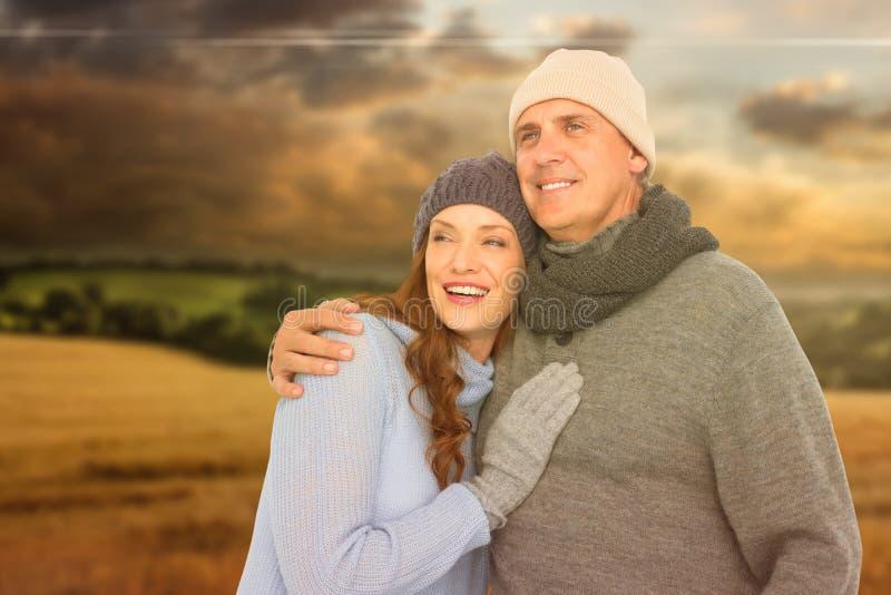 Samengesteld beeld van paar in het warme kleding omhelzen stock afbeelding
