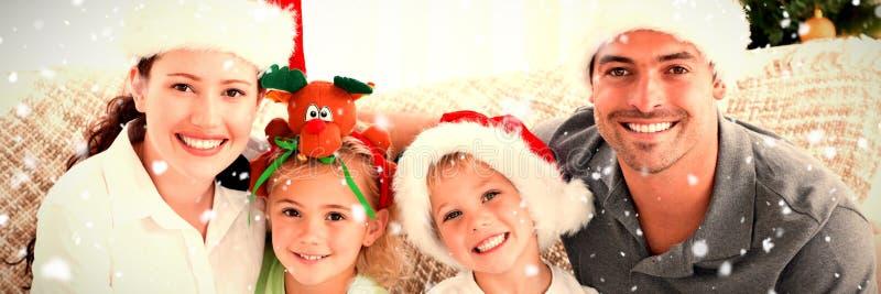 Samengesteld beeld van portret van een gelukkige familie die met Kerstmishoeden op de bank zitten royalty-vrije stock fotografie