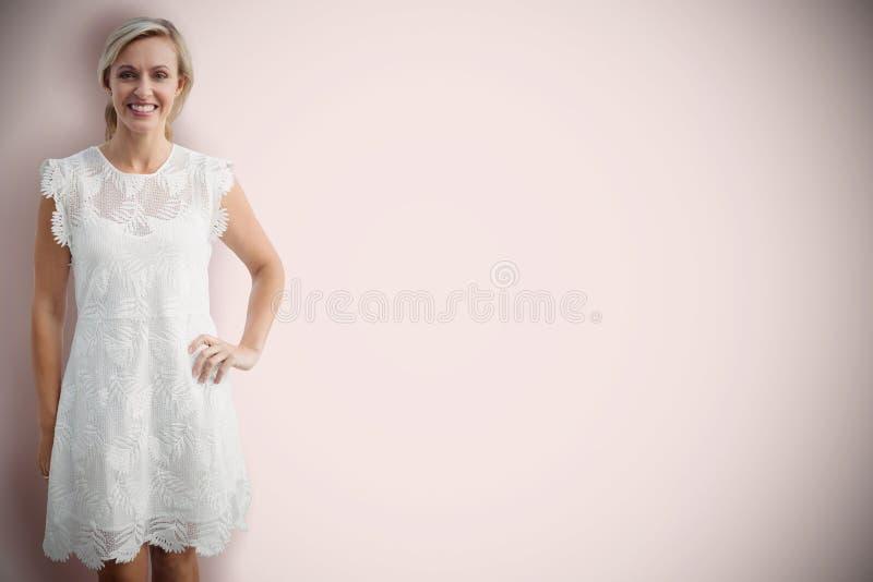 Samengesteld beeld van portret van glimlachende blondevrouw tegen witte achtergrond stock foto