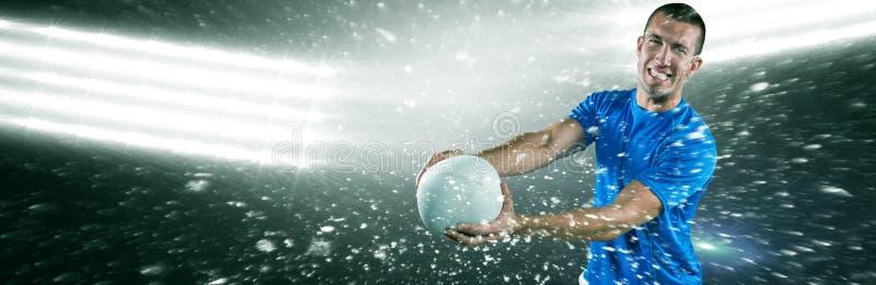 Samengesteld beeld van portret van glimlachende rugbyspeler in blauwe de holdingsbal van Jersey stock afbeelding