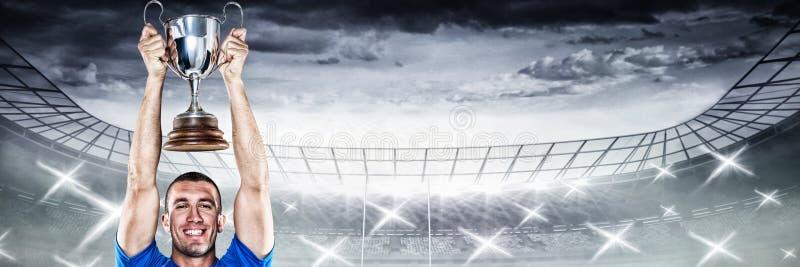 Samengesteld beeld van portret van het glimlachen van de holdingstrofee van de rugbyspeler stock afbeeldingen