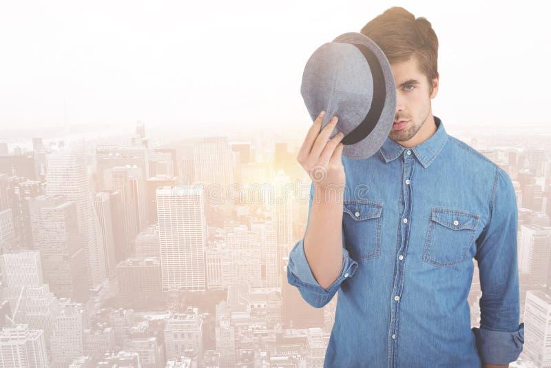 Samengesteld beeld van portret van de hoed van de hipsterholding voor gezicht stock foto's
