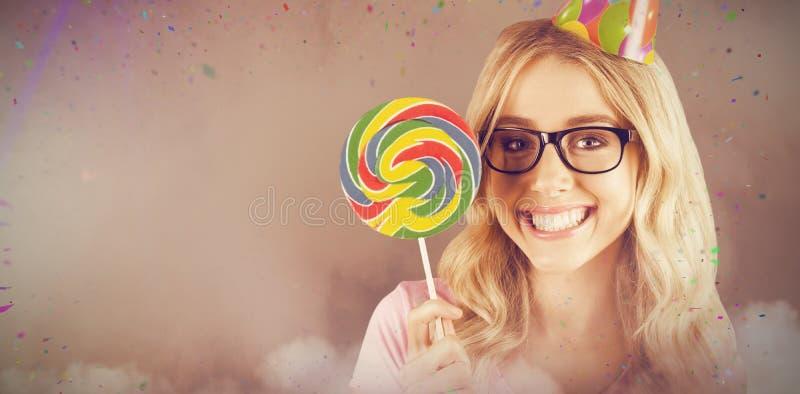 Samengesteld beeld van portret van een hipster met een partijhoed die een lolly houden stock fotografie