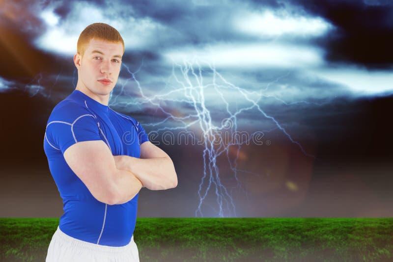 Samengesteld beeld van portret van een rugbyspeler met gekruiste wapens stock foto's