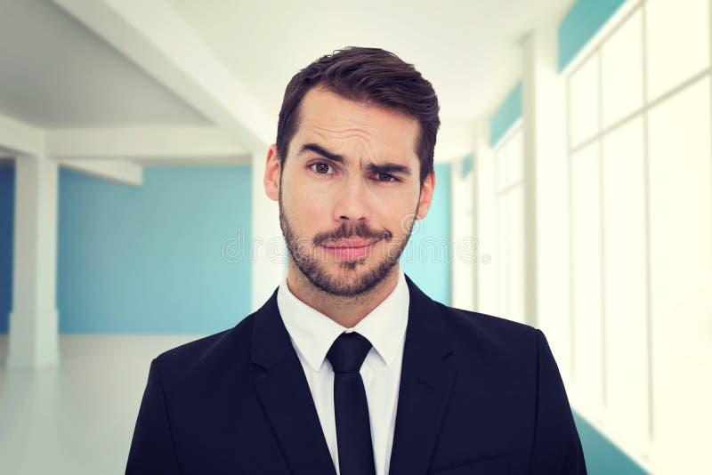 Samengesteld beeld van portret van een sceptische goed geklede zakenman stock foto