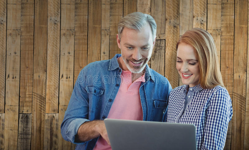 Samengesteld beeld van portret van glimlachende bedrijfsmensen die laptop met behulp van royalty-vrije stock afbeeldingen