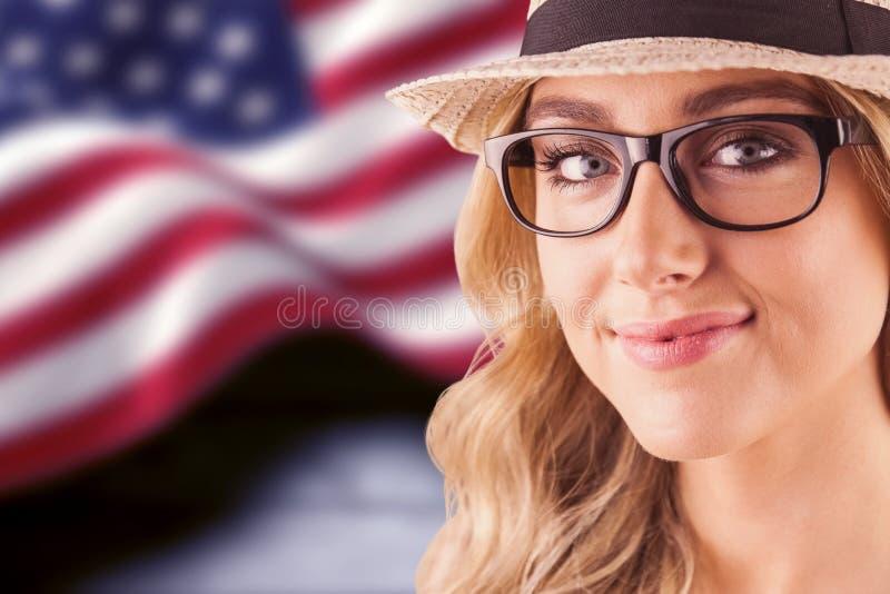 Samengesteld beeld van schitterend blonde die hipster glimlachen stock foto