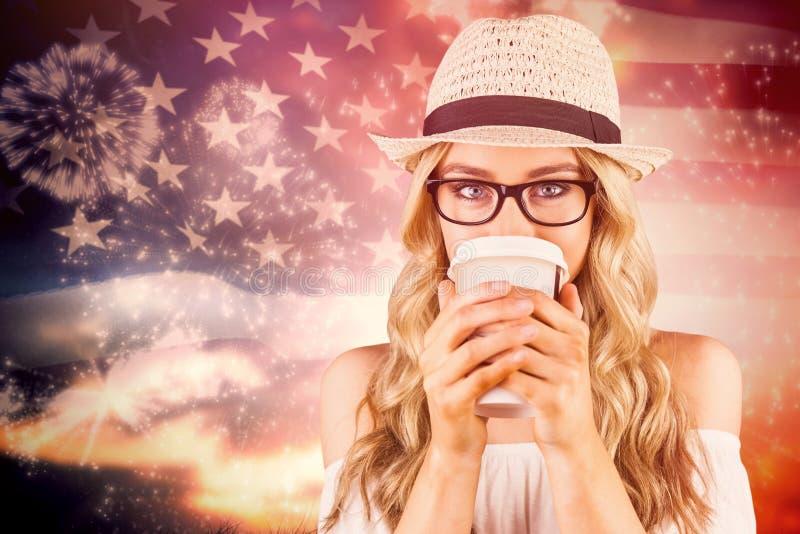 Samengesteld beeld van schitterend blonde die hipster uit meeneemkop drinken royalty-vrije stock afbeelding