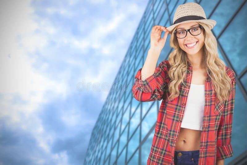 Samengesteld beeld van schitterend glimlachend blonde die hipster stellen stock afbeelding