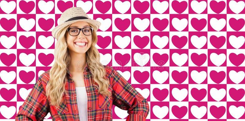 Samengesteld beeld van schitterend glimlachend blonde hipster met handen op heupen stock fotografie