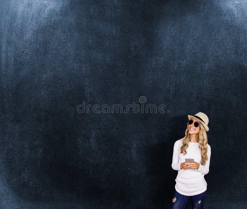 Samengesteld beeld van schitterende het glimlachen smartphone van de blonde hipster holding royalty-vrije stock afbeeldingen