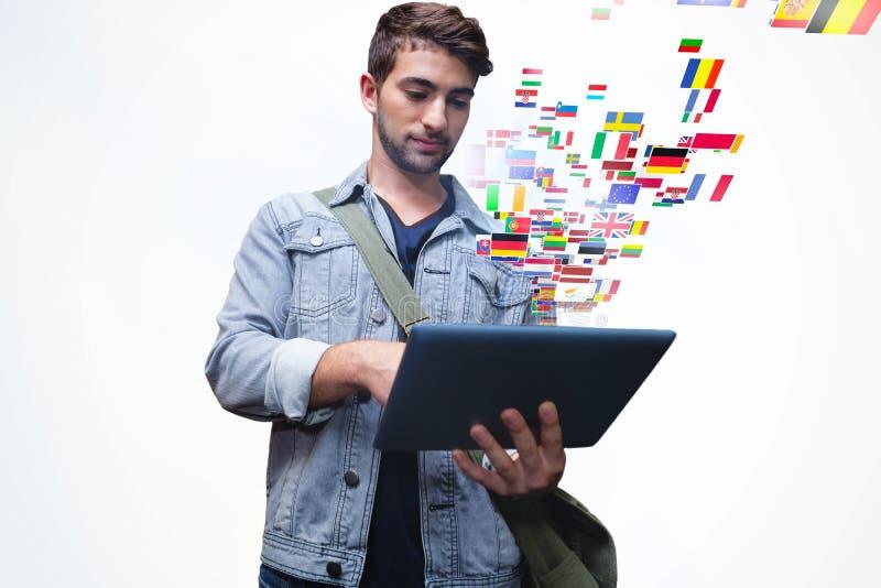 Samengesteld beeld van student die tablet in bibliotheek gebruiken stock foto's