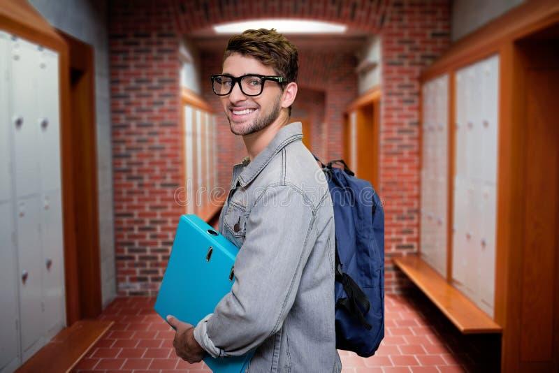 Samengesteld beeld van student het glimlachen bij camera in bibliotheek stock foto