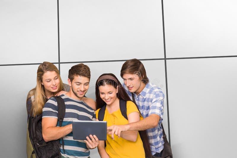 Samengesteld beeld van studenten die digitale tablet gebruiken bij universiteitsgang stock foto's