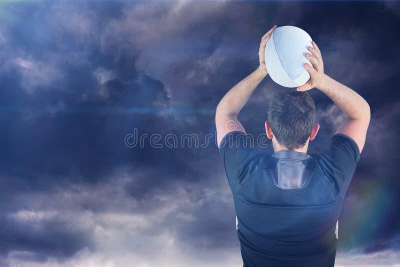 Samengesteld beeld van terug gedraaide rugbyspeler die een 3D bal werpen stock foto