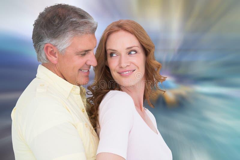 Samengesteld beeld van toevallig en paar die koesteren glimlachen stock foto