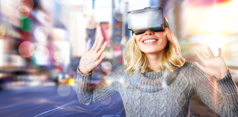 Samengesteld beeld van vrolijke jonge vrouw die werkelijkheids virtuele hoofdtelefoon met behulp van stock foto