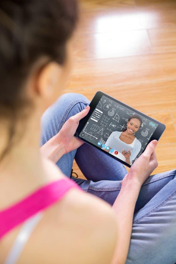 Samengesteld beeld van vrouw die tablet thuis gebruiken royalty-vrije stock foto