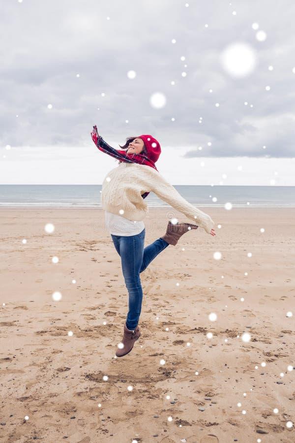 Samengesteld beeld van vrouw in modieuze warme kleding die bij strand springen stock fotografie