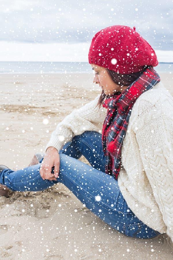 Samengesteld beeld van vrouw in modieuze warme kledingszitting bij het strand stock foto's