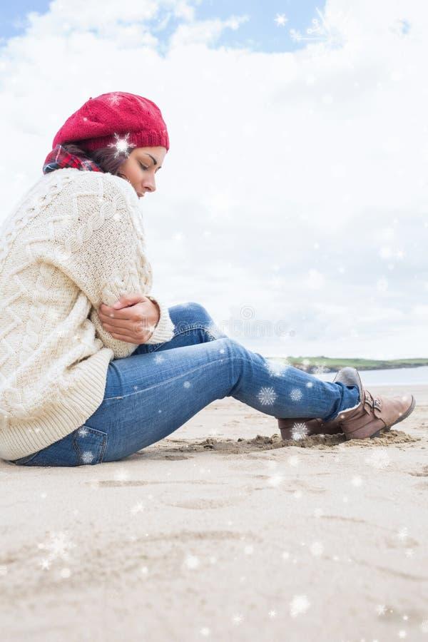 Samengesteld beeld van vrouw in modieuze warme kledingszitting bij strand royalty-vrije stock foto's