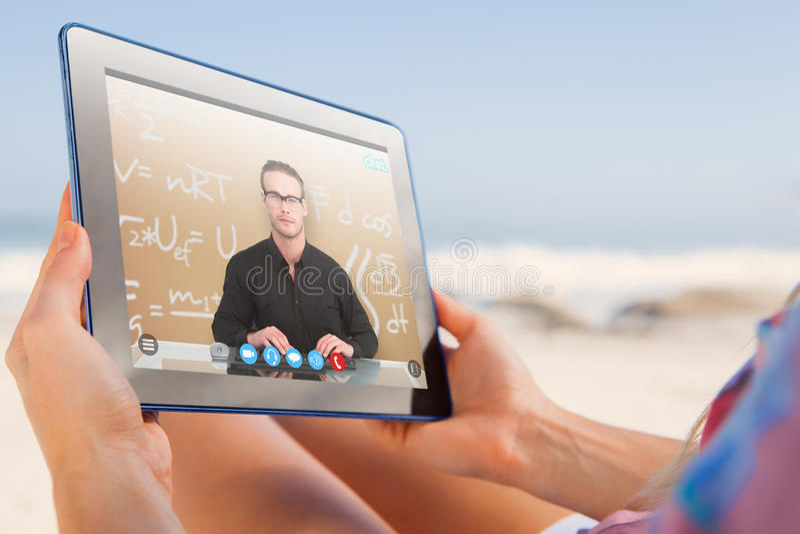 Samengesteld beeld van vrouwenzitting op strand in ligstoel die tabletpc met behulp van stock afbeeldingen