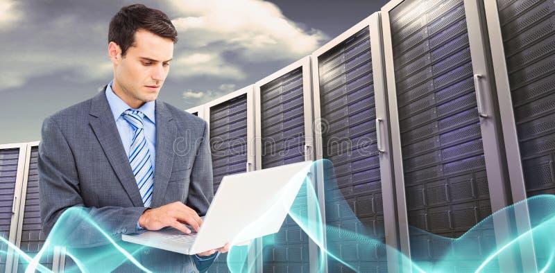 Samengesteld beeld van zakenman die laptop met erachter collega's met behulp van royalty-vrije stock fotografie
