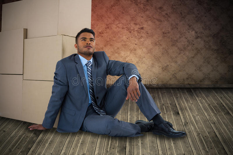 Samengesteld beeld van zakenman het leunen op kartondozen tegen witte achtergrond royalty-vrije stock afbeelding